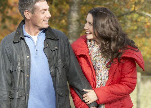 Young Couple Walking Through Autumn Park