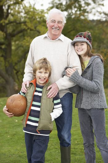 Grandfather With Grandchildren Holding Football Outside