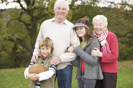 Grandparents With Grandchildren Holding Football Outside