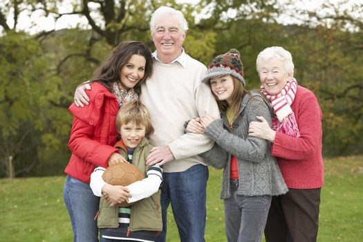 Grandparents With Grandchildren And Mother  Holding Football Outside