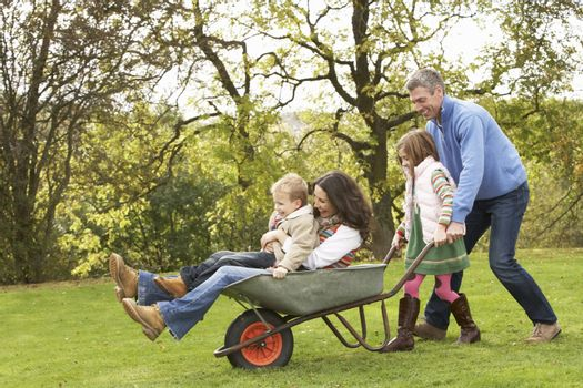 Family With Man Giving Mother And Children Ride In Wheelbarrow