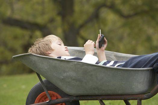 Young Boy Laying Wheelbarrow Using Smart Mobile Phone