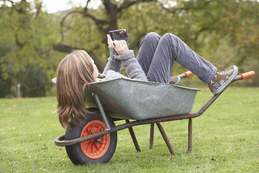 Young Girl Laying Wheelbarrow Using Smart Mobile Phone
