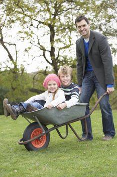 Father Giving Children Ride In Wheelbarrow