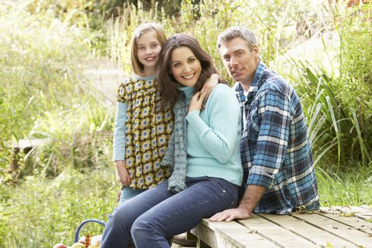 Parents And Daughter Having Picnic In Countryside