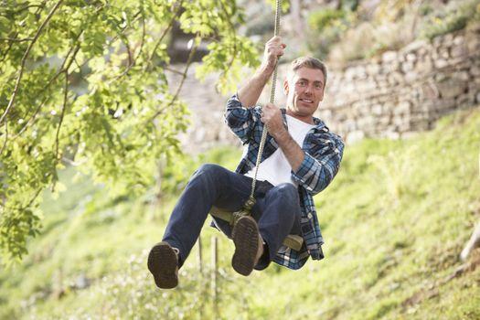Man Having Fun On Woodland Swing In Autumn