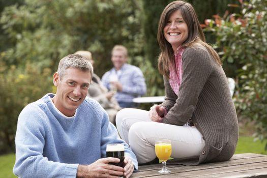 Couple Outdoors Enjoying Drink In Pub Garden