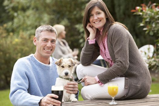 Couple With Pet Dog Outdoors Enjoying Drink In Pub Garden