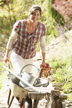 Woman With Wheelbarrow Working Outdoors In Garden