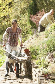 Couple With Wheelbarrow Working Outdoors In Garden