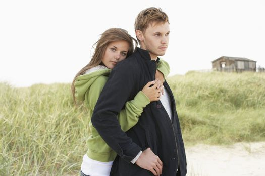 Romantic Young Couple Standing By Dunes With Beach Hut In Distan