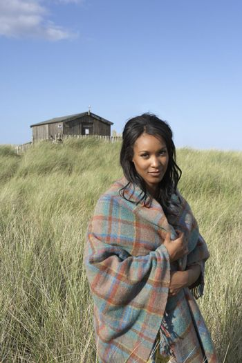 Young Woman Standing On Beach Wrapped In Blanket With Beach Hut