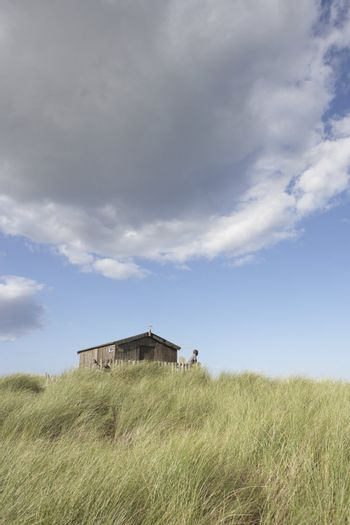 Distant View Of Young Couple Relaxing In Wooden Beach Hut Amongs