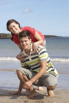 Affectionate Teenage Couple Having Fun On Beach