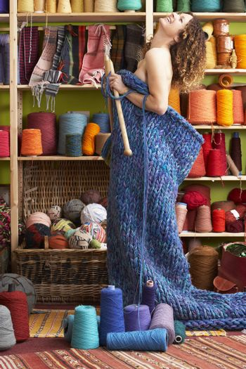 Naked Woman Standing In Knitted Item Standing In Front Of Yarn D