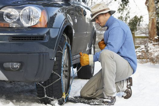 Man Putting Snow Chains Onto Tyre Of Car