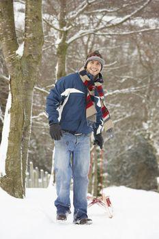 Man Pulling Sledge Through Winter Landscape