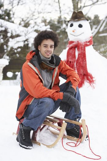Man With Sledge Next To Snowman