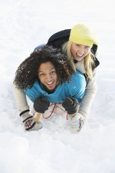 Couple Sledging Through Snowy Woodland