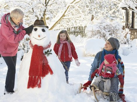 Young Girl With Grandmother And Mother Building Snowman In Garde