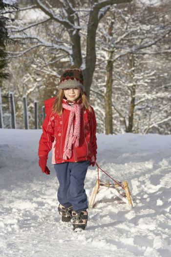 Young Girl Pulling Sledge Through Snowy Landscape