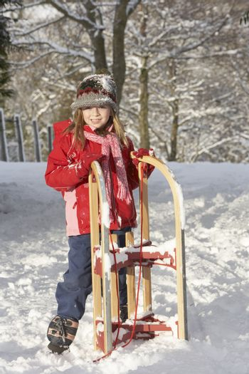 Young Girl Holding Sledge In Snowy Landscape