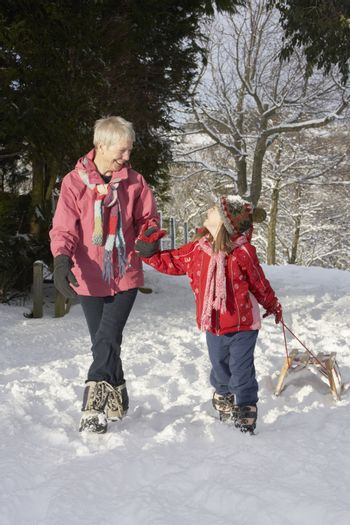 Young Girl With Grandmother Pulling Sledge Through Snowy Landsca