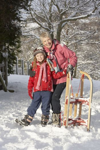 Young Girl With Grandmother Holding Sledge In Snowy Landscape