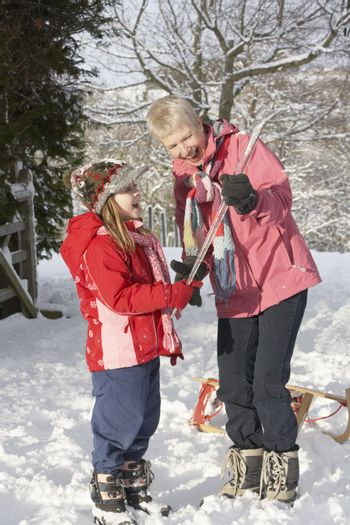 Young Girl Showing Grandmother Icicle In Snowy Landscape