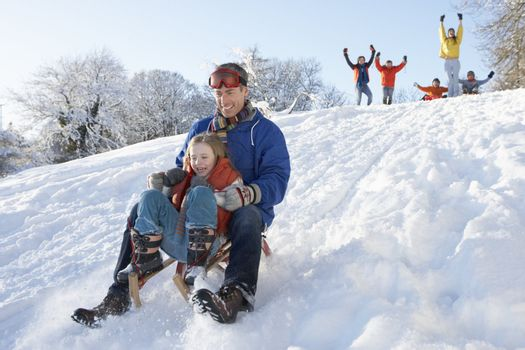 Father And Daughter Having Fun Sledging Down Hill
