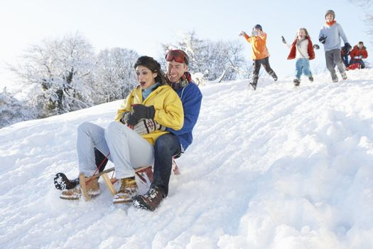 Young Couple Sledging Down Hill With Family Watching