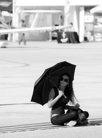 LUQA, MALTA - SEP 26 - A female spectator shades herself from the hot sun and sits down on the tarmac during the Malta International Airshow 26th September 2009