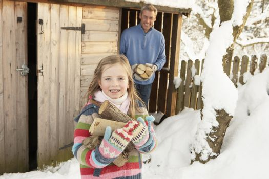 Father And Daughter Collecting Logs From Wooden Store In Snow