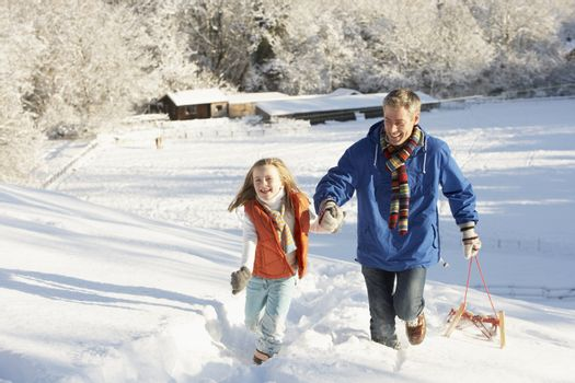 Father And Daughter Pulling Sledge Up Snowy Hill