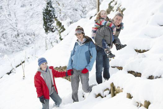 Family Enjoying Walk Through Snowy Landscape