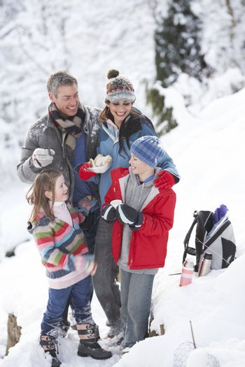 Family Stopping For Hot Drink And Snack On Walk Through Snowy La