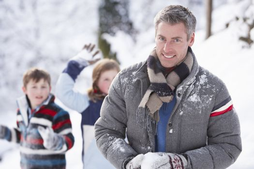 Father And Children Having Snowball Fight In Winter Landscape