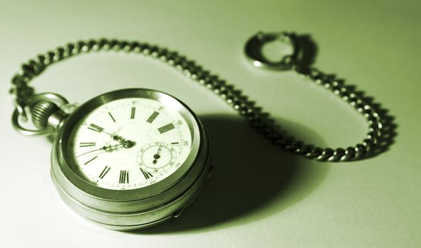 old silver pocket watch; focused on the dial; with a chain, tinted green; gradient background