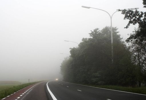 Misty main road with car headlights visible through the mist