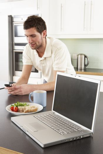 Young Man With Laptop In Modern Kitchen About To Eat Meal
