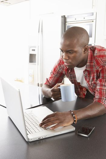 Young Man Using Laptop In Modern Kitchen
