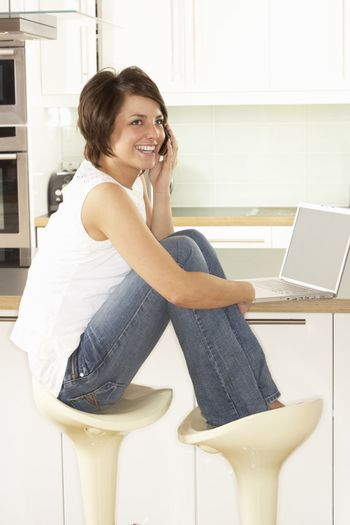 Young Woman Relaxing Sitting In Kitchen Talking On Phone
