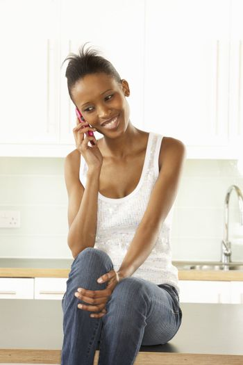 Woman Using Mobile Phone Sitting In Modern Kitchen