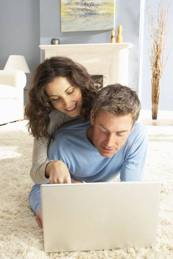 Couple Using Laptop Relaxing Laying On Rug At Home