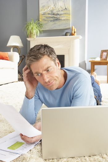 Man Using Laptop To Manage Household Bills Laying On Rug At Home