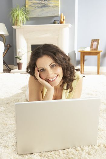 Woman Using Laptop Relaxing Laying On Rug At Home