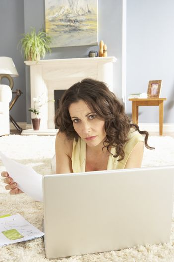 Woman Using Laptop To Manage Household Bills Laying On Rug At Home