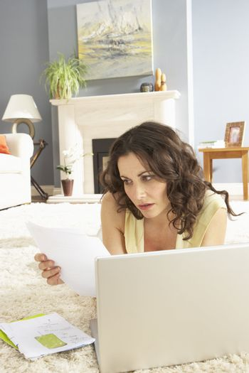 Woan Using Laptop To Manage Household Bills Laying On Rug At Home