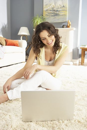 Woman Using Laptop Relaxing Sitting On Rug At Home