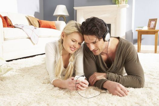 Couple Listening To MP3 Player On Headphones Relaxing Laying On Rug At Home